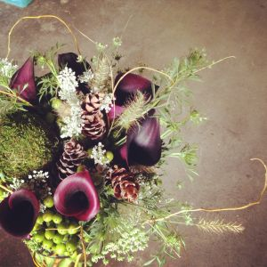 a wedding bouquet with purple flowers, pinecones, and greenery