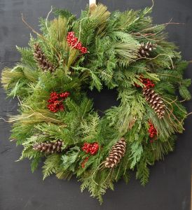 a wreath with pinecones and red berries