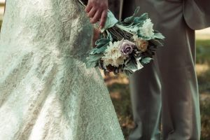 lower half of bride holding a bouquet and groom