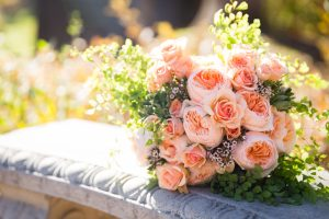 wedding bouquet with peach roses and greenery on a bench