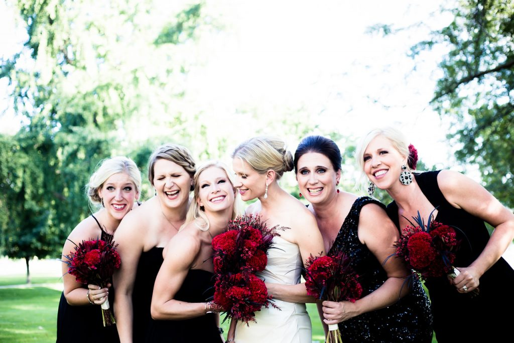 bridal party holding red bouquets
