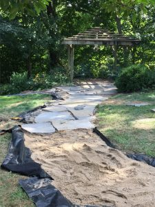 flagstone pathway being built to pergola