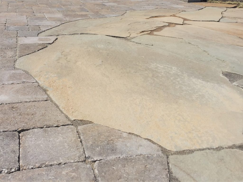 A close up of a patio made from pavers and flagstone