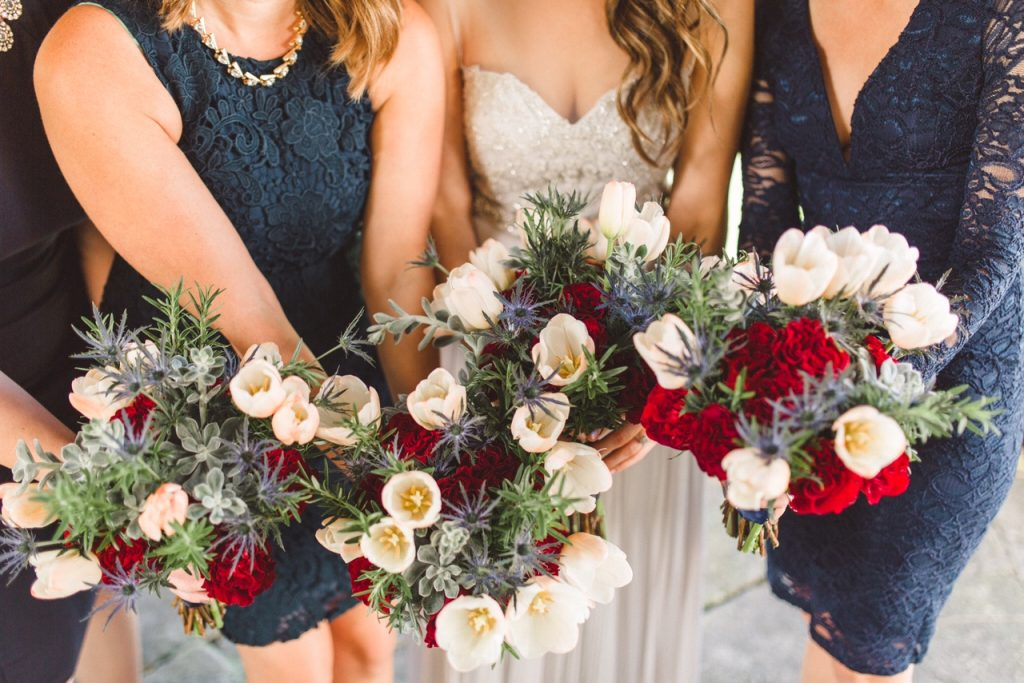 Bridal party with red, white, and blue bouquets